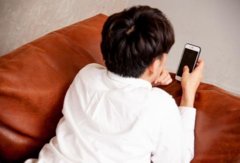 男性がスマートフォンをさわっている画像