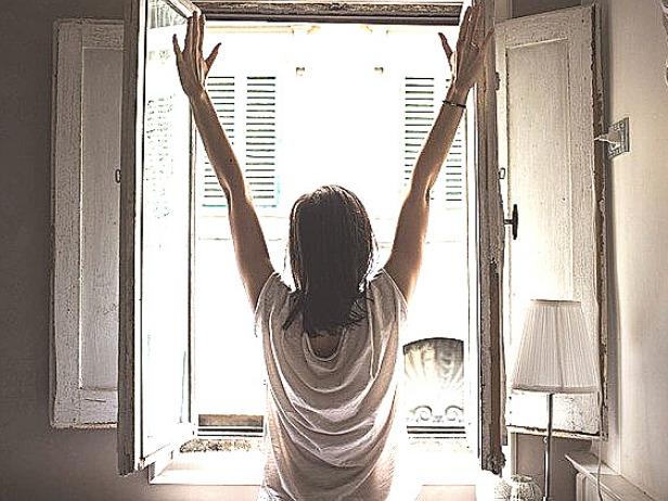 起床後に朝日を浴びる女性