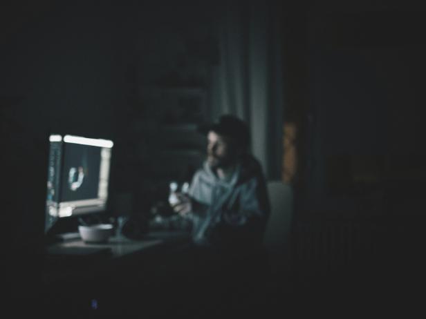 暗闇でPCを使用する男性