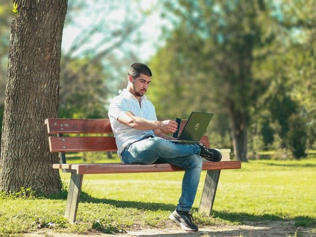 屋外でPCを使用する男性